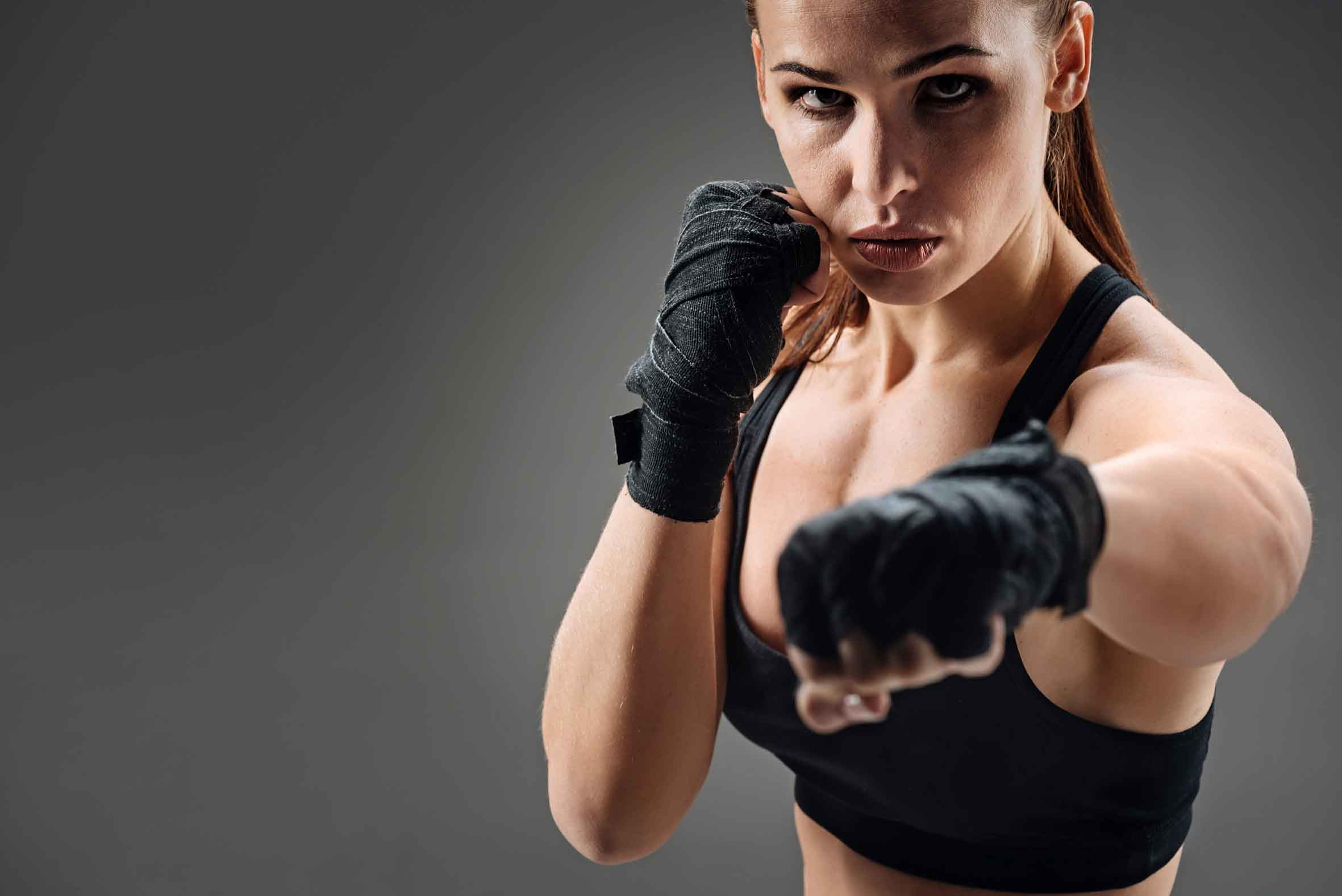 Joyful woman boxing on a grey background